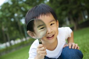 young boy looking through magnifying glass