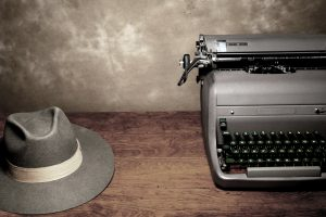 manual typewriter and man's fedora on desk