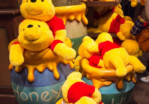 Winnie the Pooh stuffed toys and honey jars in a store