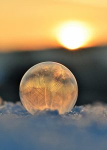 frozen ball of ice on snow with sunrise behind