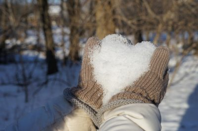 mittened hands holding snow in shape of heart