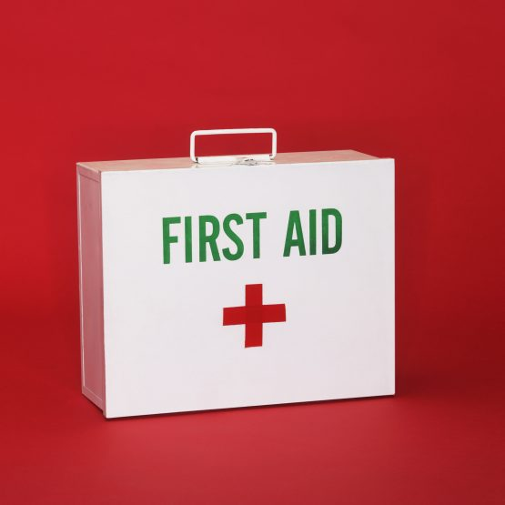 closed first aid kit on red background