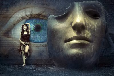 fantasy image young woman in front of painting of eye and beside sculpture of partial face