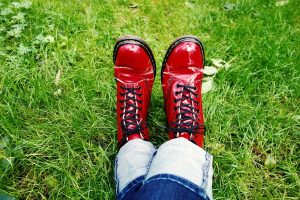 woman's feet in red boots grass background