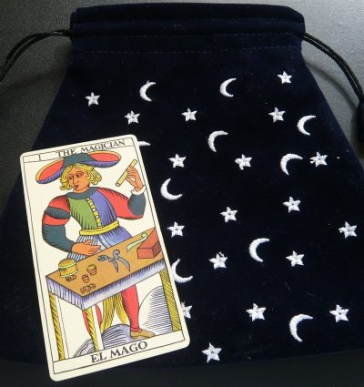 Tarot card of magician and black bag with stars and moons