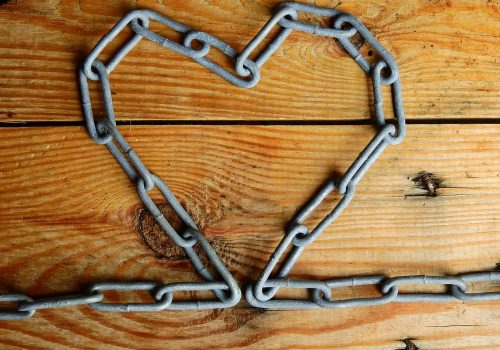 chain forming a heart, a constant connection, against wood background