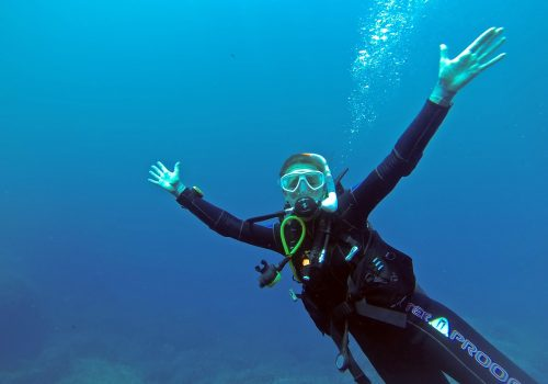 female scuba diver in water, arms extended