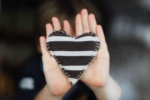 black and white striped fabric heart held up by child's hands
