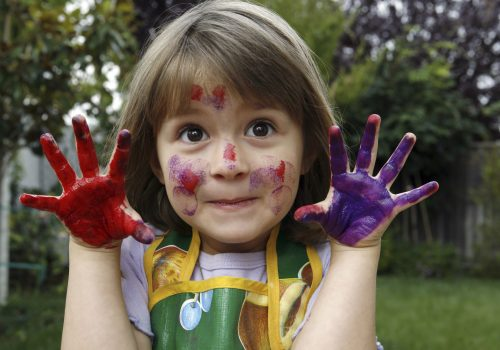 Young happy girl, hands and face covered in paint