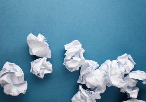 crumpled white paper on blue background