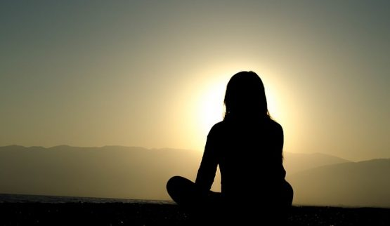 silhouette of seated woman seeking self-understanding in sun