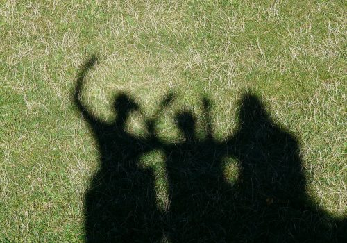 shadows of three women on grass