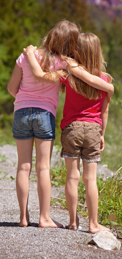 backs of two young girls arms around each other