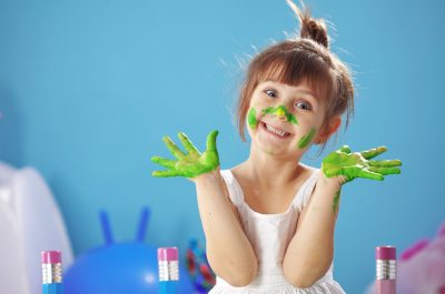 happy young girl with fingerpainted hands and nose